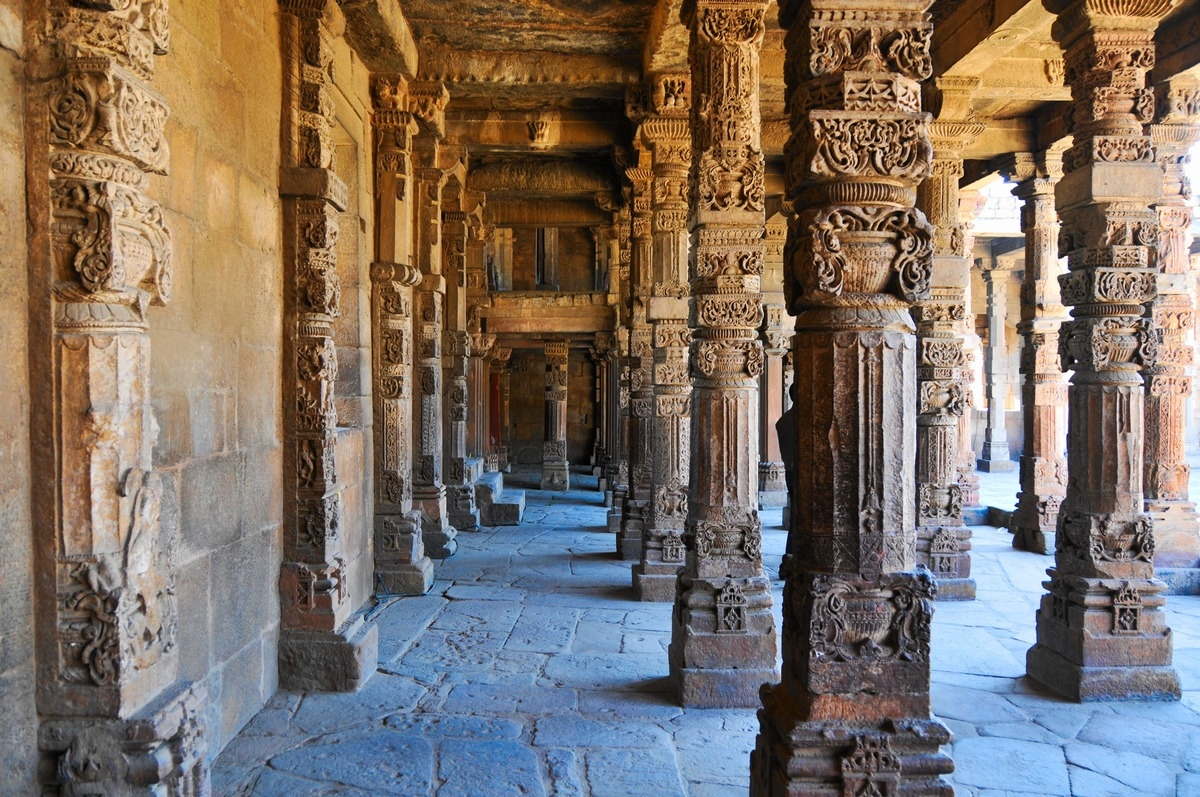 Rows of stone pillars with carvings among the archeological ruins from 13th century India.