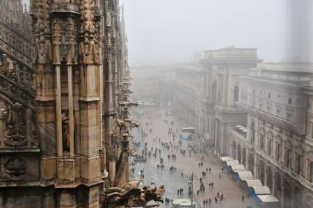 a rainy and foggy morning at the duomo in milan: view from the top of the duomo in milan on rainy morning