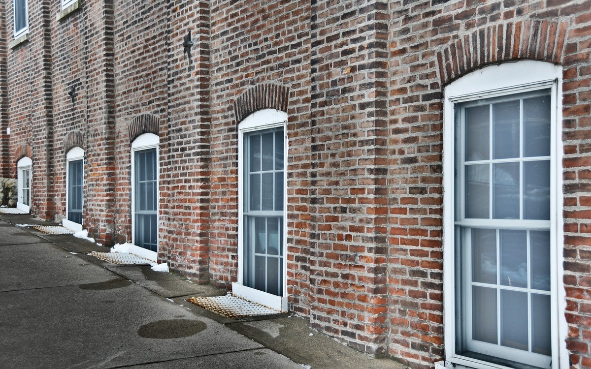 five white windows that line the red brick wall along a street