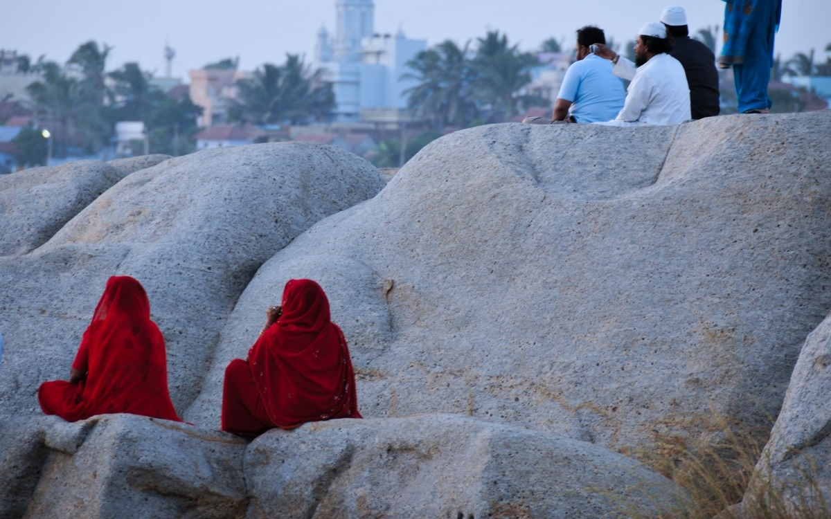two women in red sari perched on the rock looking out into the horizon