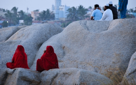 two women in red saree perched on the rock: two women in red saree perched on the rock looking out into the horizon