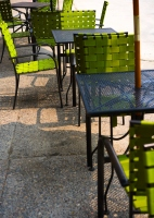 some green chairs on the pavement: outdoor seating area with some green chairs and a tables