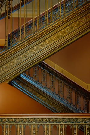 an ornate stairwell: picture of an ornate staircase inside a building in gold brown tones