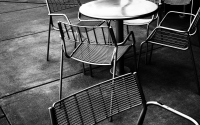 chairs and tables in black and white: metal chairs and tables on the pavement in black and white. street scene