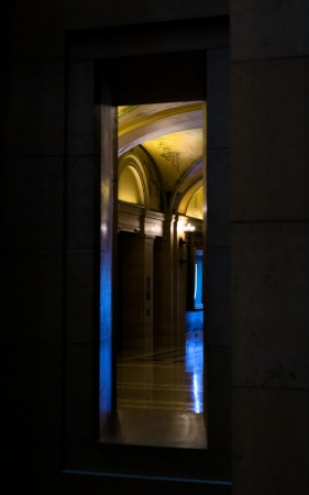 looking out to the corridor through a doorway: corridor lit by blue cold sunlight and warm yellow lights when looking out through a narrow doorway