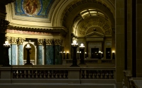 lot of lit lights in the interior of capital building in madison: interior shot of the madison capitol building with pillars and murals