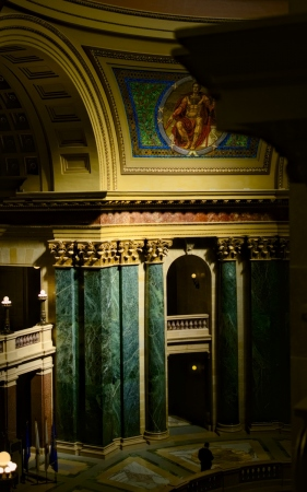 warm light and romanesque architecture : interior shot of the madison capitol building with pillars and murals