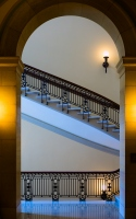 a stairwell with arch : view of a staircase framed by an archway and with warm and cold lighting