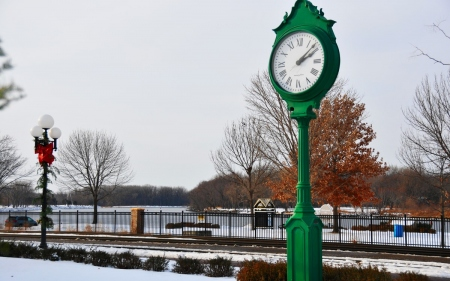 a green clock by the side of the road : a clock and street lamp a road and a river