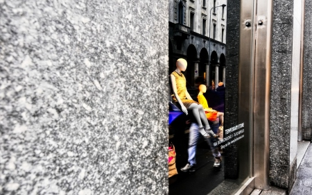 storefront window with mannequins on display and reflections of the buildings on the glass