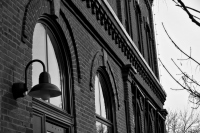 side of a brick building with arch windows in black and white