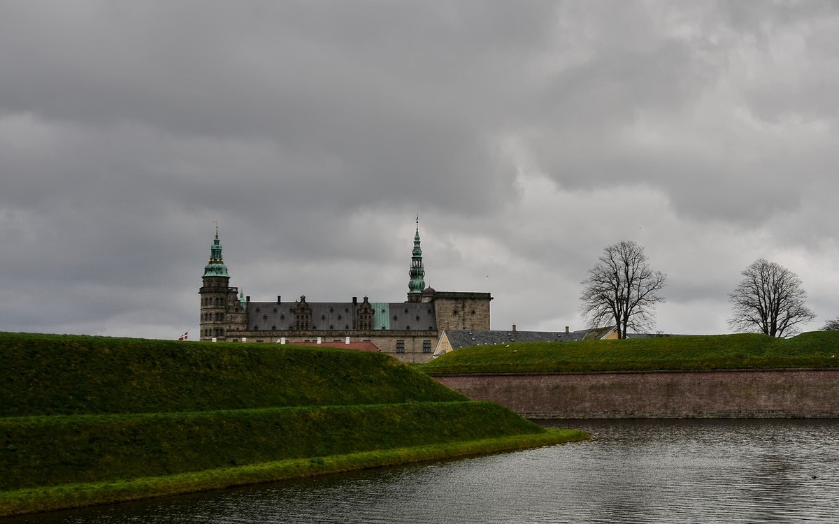 the kornborg castle in denmark with the canal and green lawn