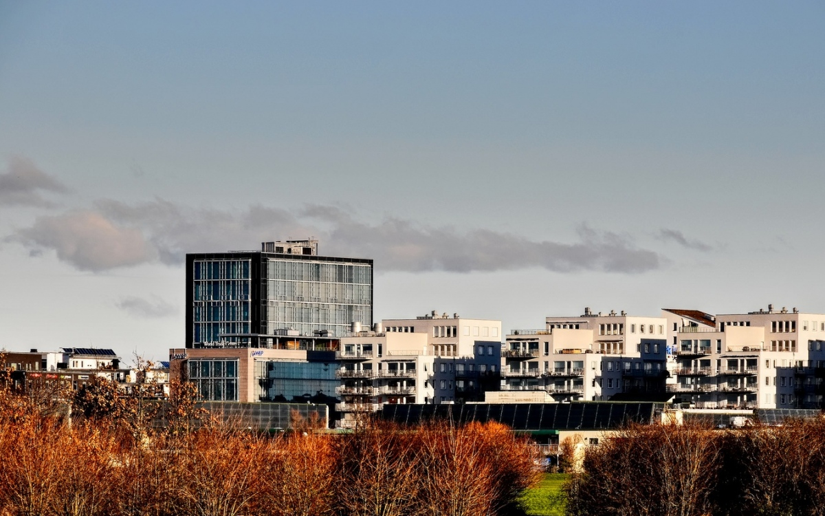 skyline of malmo city against the blue sky and red trees