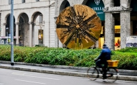 street scene with the cyclist and the sculpture in milan