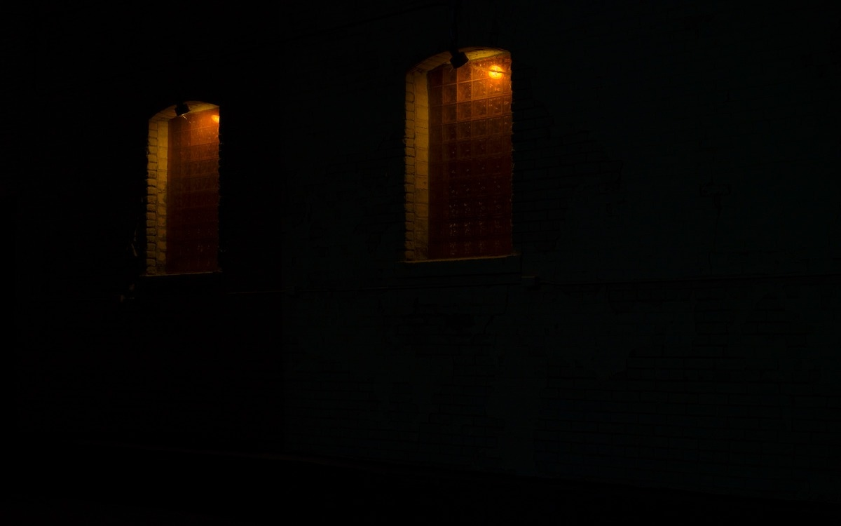 two lit windows along the dark alleyway