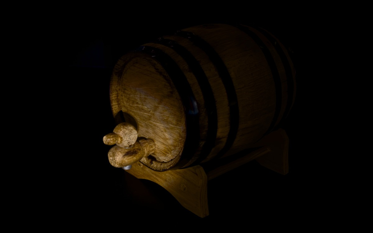 a whiskey cask in the dark lit by a single light source
