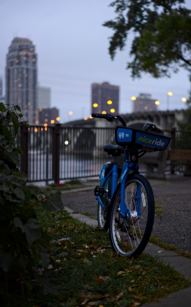 a blue bicycle by the street against the city skyline